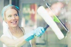 Haushälterin wischt Fenster ab lizenzfreie stockbilder