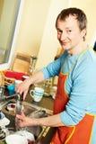 Haushälterinmann mit Tellerwaschmaschine Stockfotos