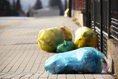 Haushaltsabfälle in den mehrfarbigen sortierenden Taschenlügen auf einer Stadtstraße nahe dem Zaun des privaten Gebiets, Export v lizenzfreie stockbilder
