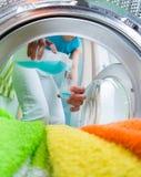 Haushaltsvorstandfrau, die Conditioner für Waschmaschine verwendet Stockfoto