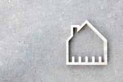 Hausikone auf konkretem Hintergrund, Wohnungsbau Lizenzfreie Stockfotos