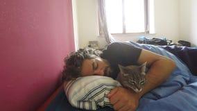 Hauskatze, die auf Bett mit schlafendem Mann liegt stock footage