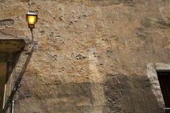 Hausmauer mit einer beleuchteten Laterne Lizenzfreie Stockbilder