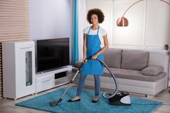 Hausmeister-Cleaning Carpet With-Staubsauger stockbilder