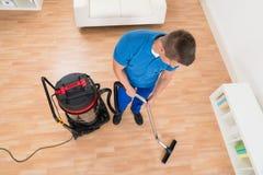 Hausmeister-Cleaning Floor With-Staubsauger Stockbilder