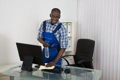Hausmeister Cleaning Glass Desk mit Stoff im Büro stockfotografie