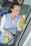 Hausmeister, der schmutziges Glas mit Chemikalie spritzt Stockfotografie