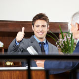 Hausmeister im Hotel, das sich Daumen zeigt Lizenzfreies Stockfoto