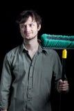 Hausmeister mit einem Besen die Stirn runzelnd an einer Verwirrung Stockfotografie