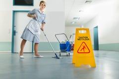 Hausmeister mit Mopp und nassem Bodenzeichen Stockbild