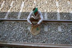 Hausmeister (Reiniger) fegt Schienenreise stockbilder
