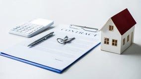 Hausmodell, Taschenrechner und Hausschlüssel, der auf Immobilien contr liegt stockbild