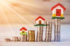 Hausmodelle auf Staplungsmünzen am Holztisch Stockfotografie