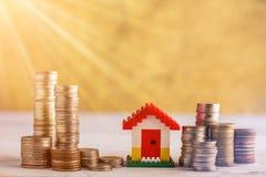 Hausmodelle auf Staplungsmünzen am Holztisch Stockfotos