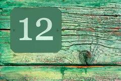 Hausnummer 12 auf der Oberfläche einer alten hölzernen grünen Tür Lizenzfreies Stockfoto