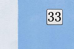 Hausnummer 33 auf einer blauen Hausmauer Lizenzfreie Stockbilder