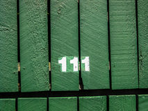 Hausnummer, 111 auf hölzernem Hintergrund Stockfotografie