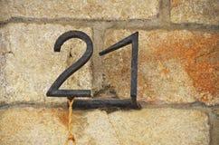 Hausnummer 21 auf rustikaler Sandsteinbacksteinmauer, rostiges Schmiedeeisenmetall nummeriert lizenzfreie stockbilder