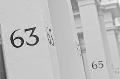 Hausnummer 63 auf weißer Säule in London Stockfotos