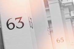 Hausnummer 63 auf weißer Säule in London Lizenzfreie Stockfotos