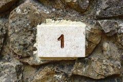 Hausnummer 1 graviert im Stein Stockbild
