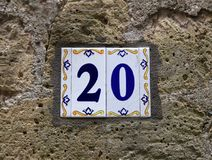 Hausnummer zwanzig 20: Keramikfliesen mit blauen Zahlen auf alter Steinwand Lizenzfreie Stockfotografie