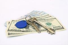 Hausschlüssel über den hundert Dollarbanknoten Lizenzfreie Stockfotografie