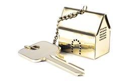 Hausschlüssel mit einem goldenen Musterhaus als keychain, lokalisiert auf whi Stockbild