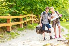 Hausse de la carte se baladante de lecture de couples en voyage Photographie stock