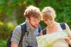 Hausse de la carte se baladante de lecture de couples en voyage Images stock