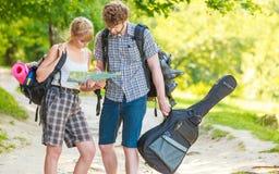 Hausse de la carte se baladante de lecture de couples en voyage Image stock