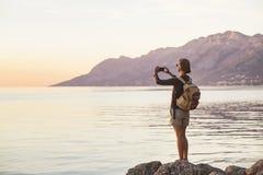 Hausse de la femme ? l'aide du t?l?phone intelligent Les vacances, amusement d'?t?, appr?cient la vie, le voyage et le concept ac photo libre de droits