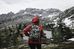 Hausse de la fille dans les montagnes détendant dans l'avant à un lac silencieux illustration stock
