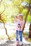 Hausse de la fille de gosse recherchant la main dans la tête dans la forêt Photos libres de droits