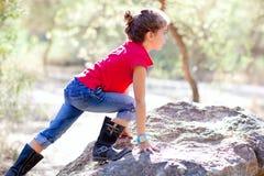 Hausse de la petite fille montant une roche dans la forêt photos libres de droits
