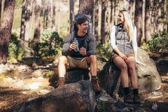Hausse de se reposer de détente de couples sur des roches pendant le trekking Image libre de droits