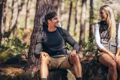 Hausse de se reposer de détente de couples sur des roches pendant le trekking Photo stock