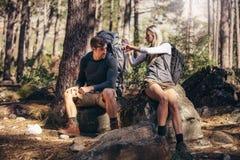 Hausse de se reposer de détente de couples sur des roches pendant le trekking Photos libres de droits