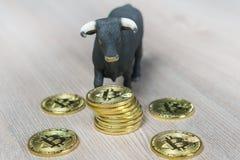 Hausse in der Schlüsselwährung Stier nahe bei Stapel bitcoin Münzen stockfotos