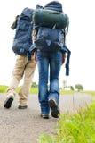 Hausse du sac à dos de pattes de couples sur la route goudronnée Image libre de droits