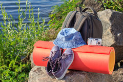 Hausse du sac à dos, des espadrilles, du chapeau, de l'appareil-photo et du tapis campant sur la roche W Image stock