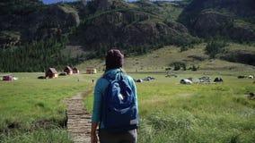 Hausse Fille de voyageur avec le sac à dos et le chapeau marchant sur un pont dans les montagnes Le camping est dans la distance  clips vidéos