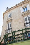 Haussmann building house covered by green plants with blue sky. A haussmann building house covered by green plants with blue sky royalty free stock image