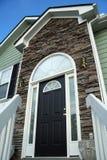 Haustür eines Hauses mit einer Steinfassade. Lizenzfreie Stockfotografie