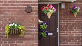 Haustür mit hängenden Blumenkörben stockfotografie