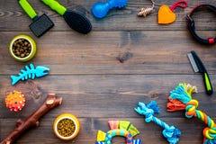 Haustierzubehör Spielwaren nahe Schüsseln mit Tierfutter, Kragen, Pflegen euqipment auf dunkler hölzerner Draufsichtkopie des Hin Lizenzfreies Stockbild