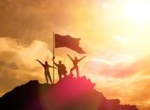 Haut accomplisseur, silhouettes de trois personnes se tenant sur une montagne pour soulever leurs mains  Photographie stock