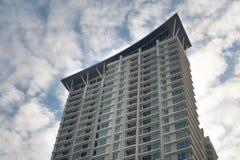 Haut bâtiment contre le ciel nuageux photo stock