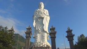 Haut Bouddha blanc se tient sur un fond de ciel bleu course de nuages à travers le ciel Timelapse banque de vidéos