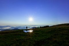 Haut dans les montagnes au-dessus des nuages un jeune homme recherche une connexion cellulaire tenant son téléphone haut images libres de droits